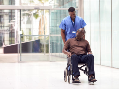 male healthcare worker assisting the old man to his appointment